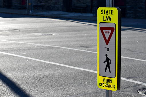 Pennsylvania Pedestrian State Law Sign in Crosswalk. Safety yield sign in Conshohocken, PA a suburb of Philadelphia.