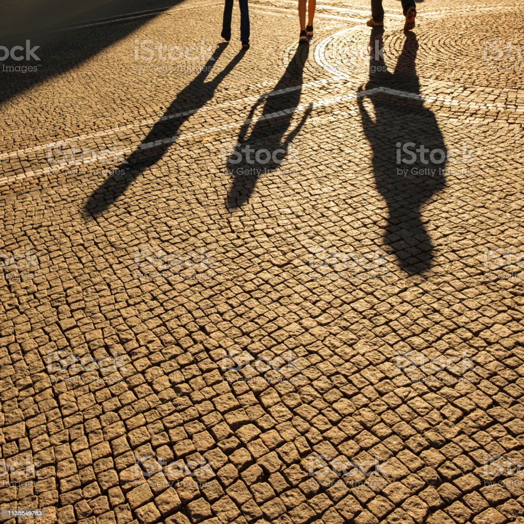 Pedestrian tourists on cooblestones in back lit with shadows