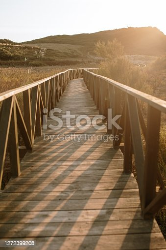 A pedestrian walkway made with wood at sunset