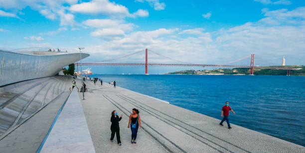 Pedestrian walkway riverside to Tagus River with view of 25 April Bridge in background stock photo