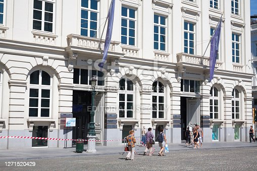 Pedestrians are passing Magritte Museum in Brussels. At facade of are flags. Museum is seated at square Place Royale