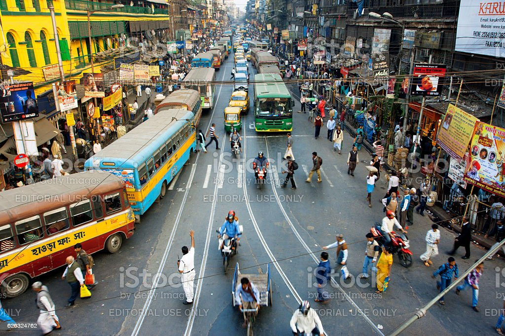 Pedestrians cross road in front of motorcycles, cars in India royalty-free stock photo