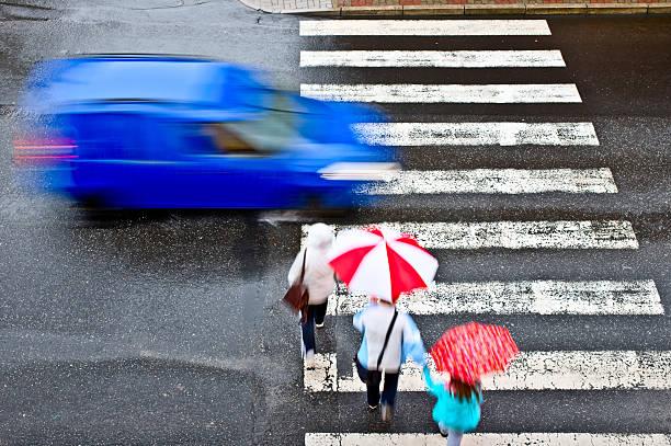 Pedestrians crossing a crosswalk in advance of a car stock photo