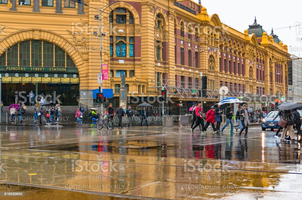 Pedestrians crossing road in front of Flinders street station on rainy day stock photo