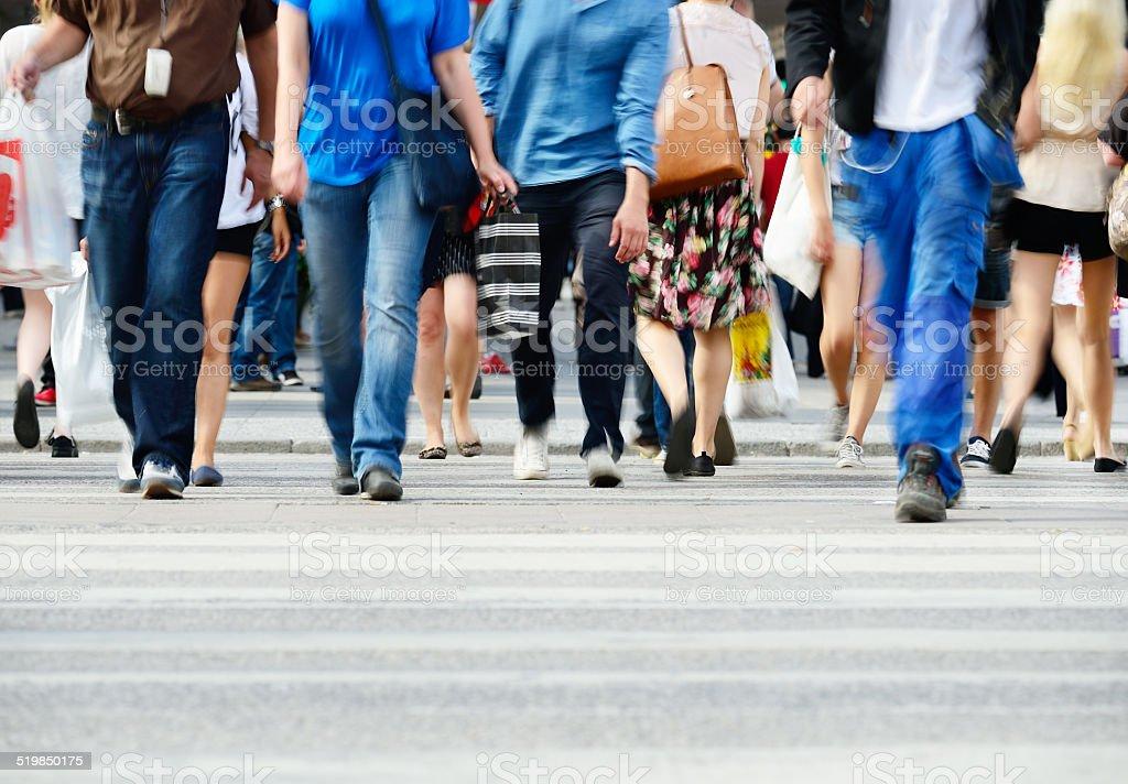 Pedestrians crossing sunlit street stock photo