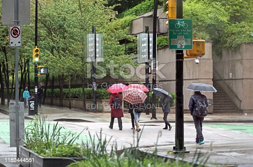 Vancouver, Canada - May 28, 2019: Pedestrians cross Smithe on a rainy morning in Vancouver. A popular bike route travels along Hornby Street through downtown. Background shows the Provincial Court of British Columbia. Canadian architect Arthur Erickson designed the Law Courts in the Robson Square complex.