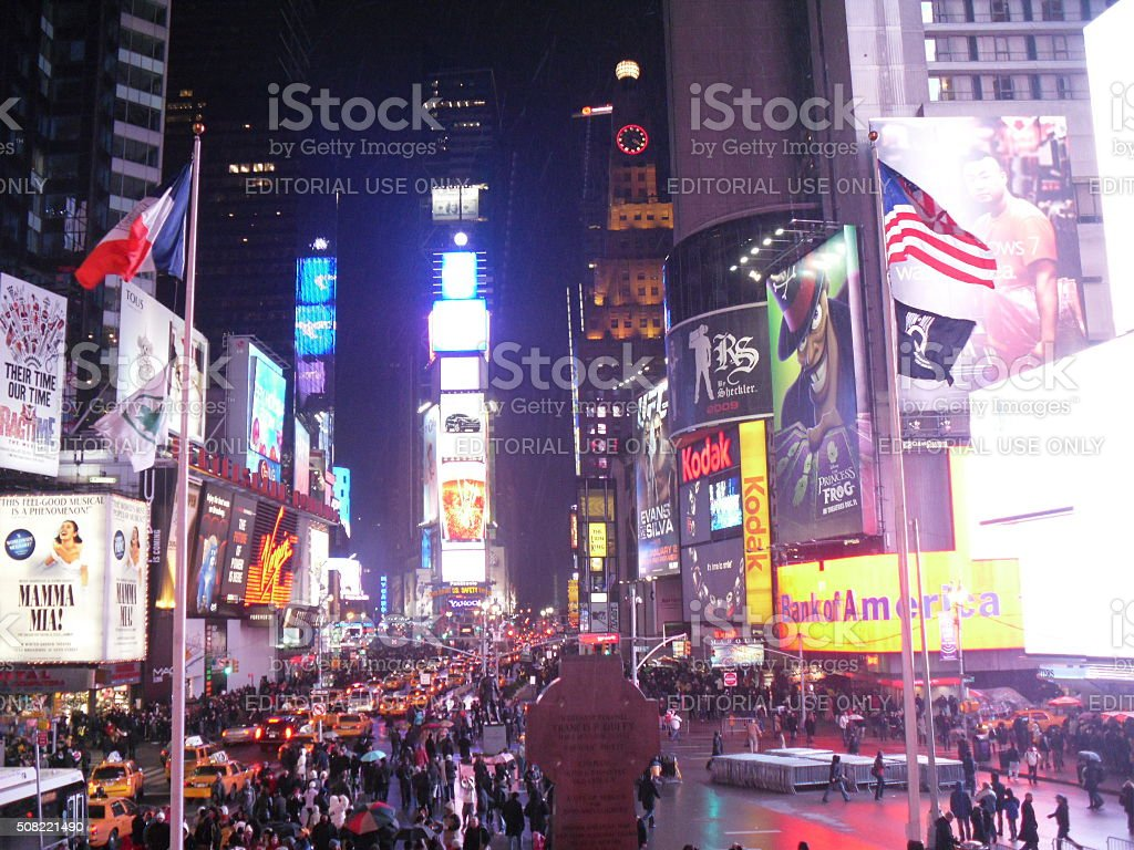 Pedestrians on Times Square in Manhattan during Rain at Night. stock photo