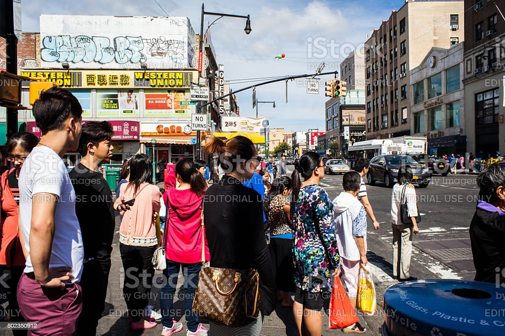Pedestrians Waiting to Cross Main Street in Flushing Queens' Chinatown stock photo