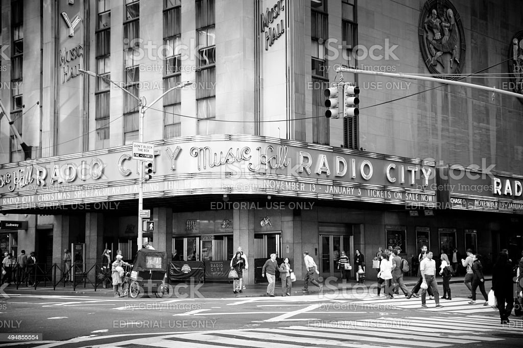 Pedestrians walk By Radio City Music Hall New York New York, United States - October 21, 2015: Pedestrians walk around and in front of Radio City Music Hall. The music hall is located in Madison Square Garden in New York City. This views shows a rickshaw driver and many pedestrians walking about.  2015 Stock Photo