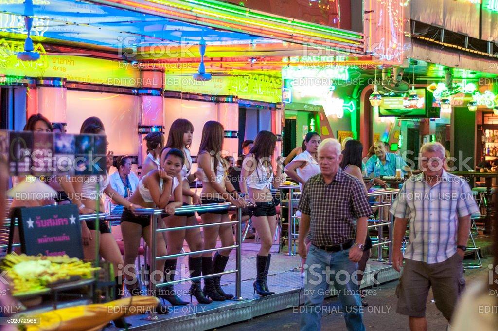 Pedestrians Walk Passed A Go-Go Bar In Soi Cowboy, Bangkok stock photo
