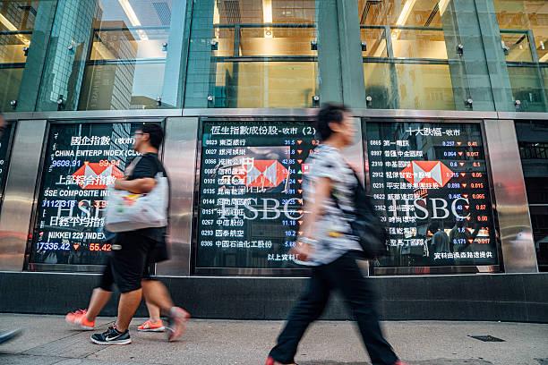 Pedestrians walk past a financial display board im Hongkong - Photo