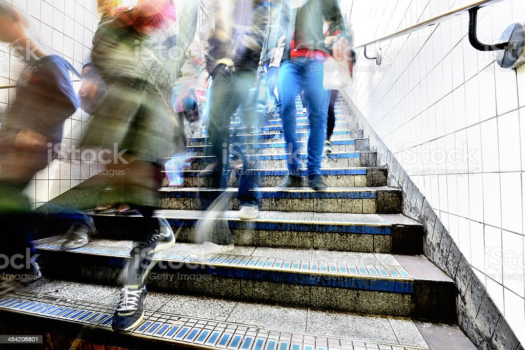 Pedestrians walking down the subway station stairs stock photo