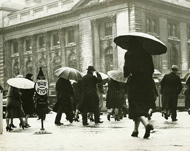 Pedestrians walking in rain in New York City, (B&W)  20th century history stock pictures, royalty-free photos & images