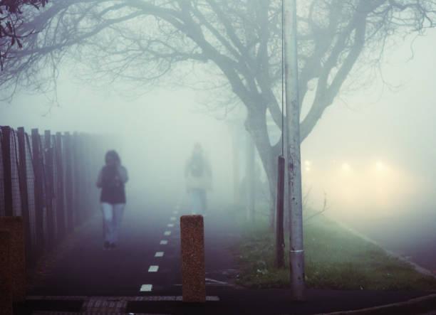 Fußgänger, die im dichten Nebel auf dem Bürgersteig laufen – Foto