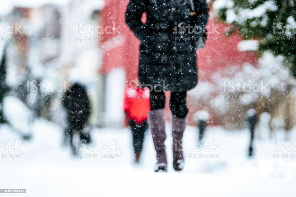 Pedestrians walking on snowy sidewalk stock photo