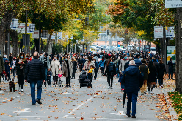 Pedestrians wearing face-covering walk on Passeo del Prado now open to pedestrians during the Covid-19 epidemic stock photo