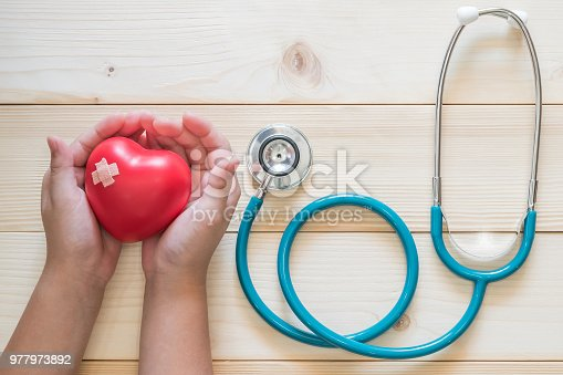 istock Pediatric care and child nursing healthcare service concept with kid patient's hands supporting red heart with medical stethoscope 977973892