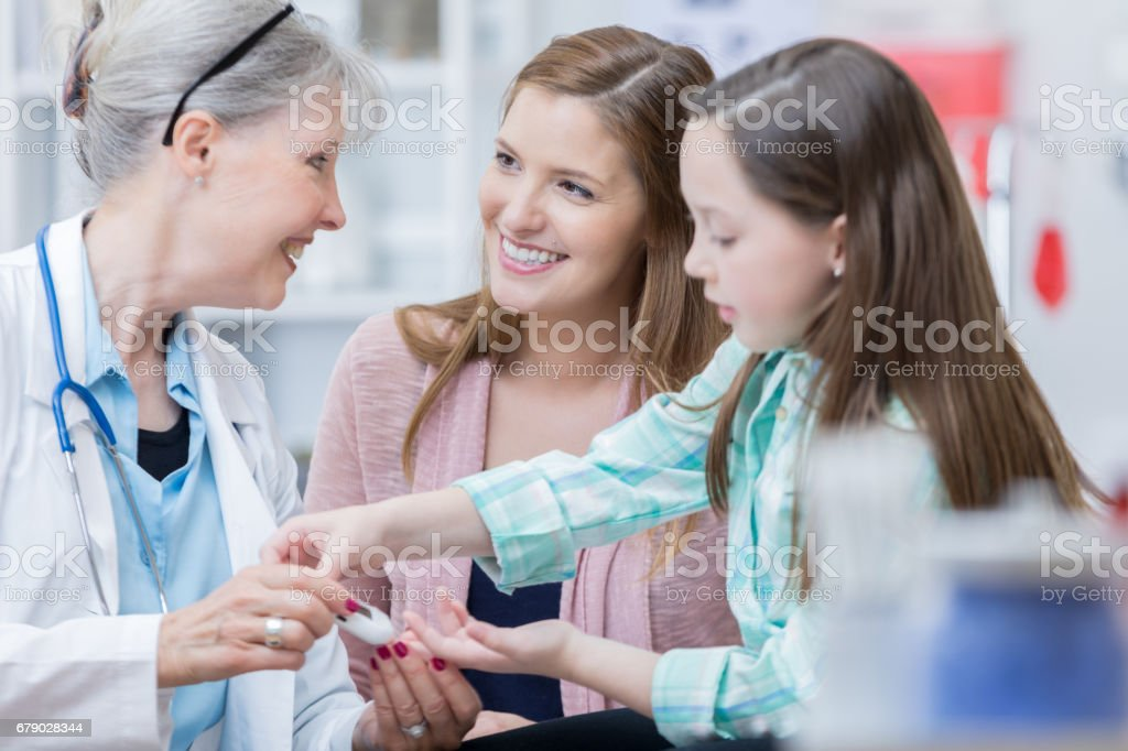 Pediatrician checks young patient's blood sugar levels stock photo