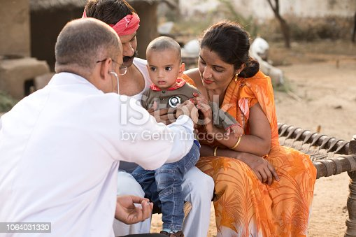 Pediatrician doctor examining ill boy during appointment at home in village