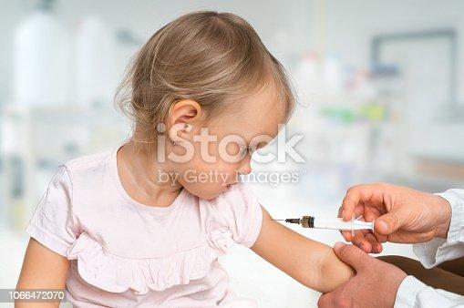 istock Pediatrician doctor is injecting vaccine to shoulder of baby 1066472070