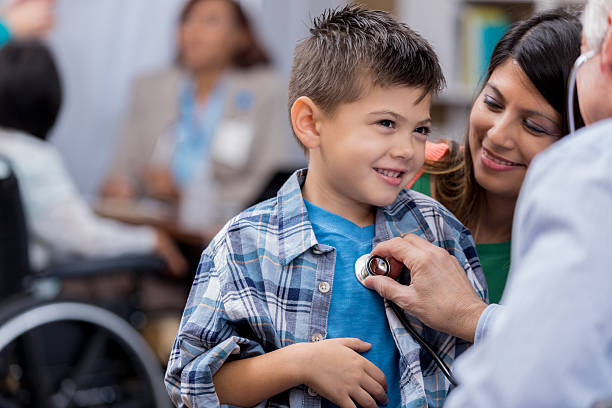 Pediatrician examines young male Hispanic patient stock photo