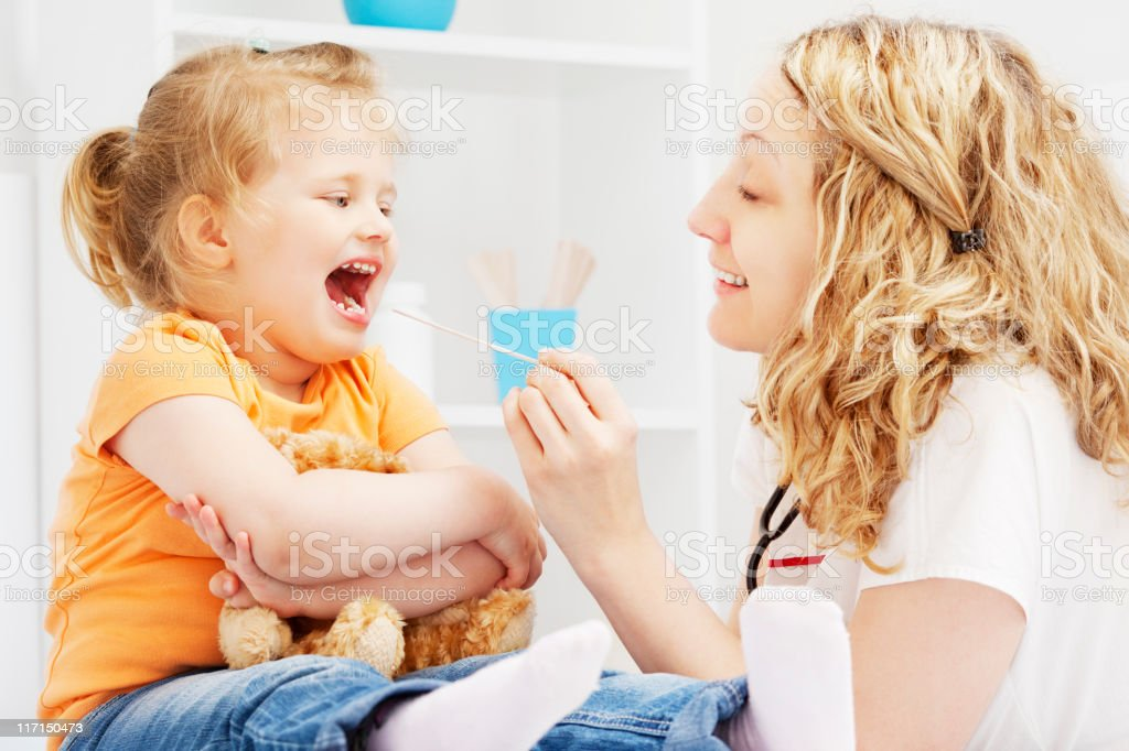 Pediatrician friendly checking little girl throat royalty-free stock photo