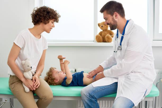 Pediatrician Palpating Stomach of Little Boy stock photo