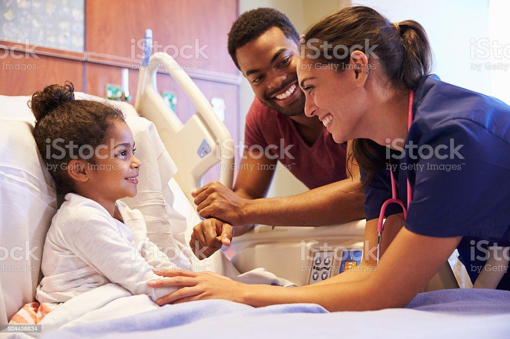 Pediatrician Visiting Father And Child In Hospital Bed stock photo