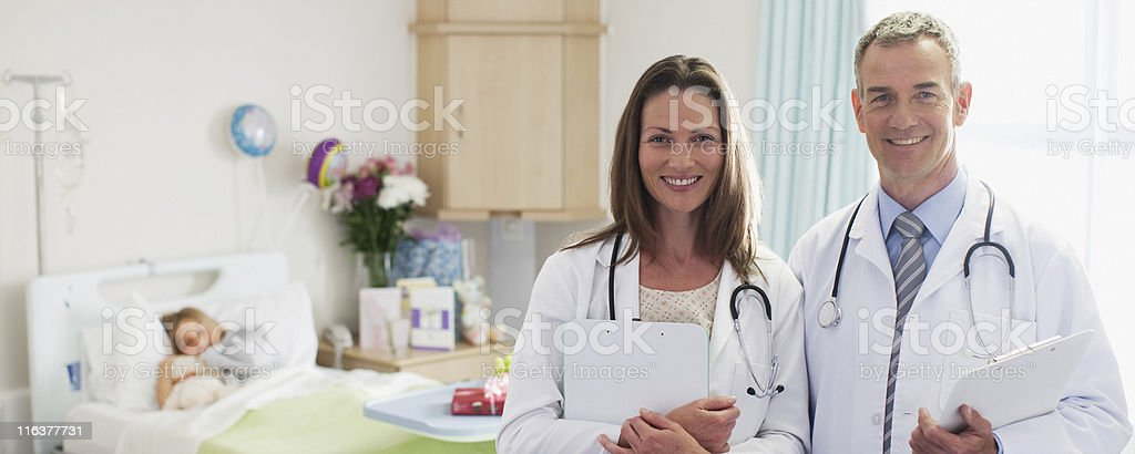 Pediatricians and patient in hospital stock photo