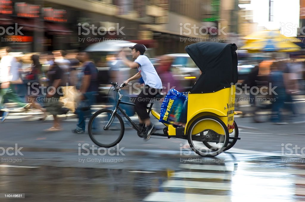 Pedicab moving quickly through pedestrians in the city stock photo
