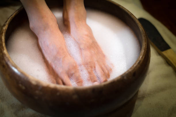 Pedicure at a beauty salon. Foot care. Feet soaking in suds water at a beauty nail spa. pedicure manicure men beauty spa stock pictures, royalty-free photos & images