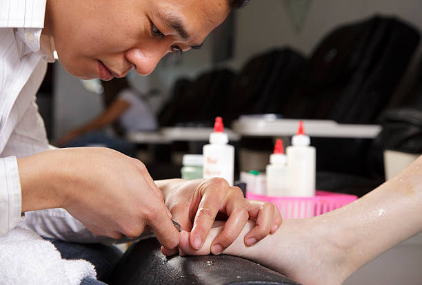 Pedicure Close Up A manicurist working in a nail salon. pedicure manicure men beauty spa stock pictures, royalty-free photos & images