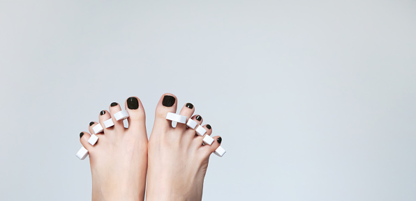 Pedicure make at home. Part of female legs on gray background with copy space. Beauty treatments