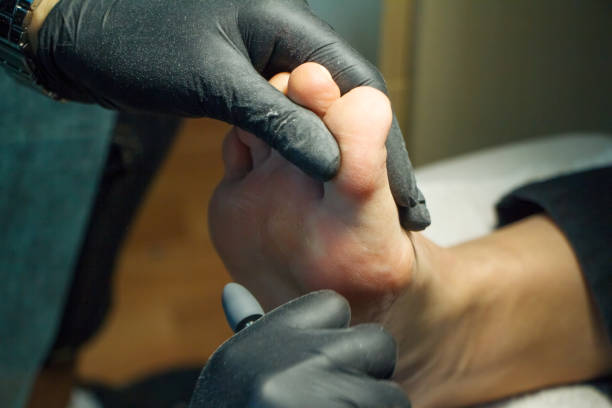 Pedicure master during work. Closeup of female feet and hands in gloves with a special machine tool. Professional hardware pedicure using electric machine.Patient on medical pedicure procedure, visiting podiatrist.Peeling feet with special electric device.Foot treatment in SPA salon.Podiatry clinic. pedicure manicure men beauty spa stock pictures, royalty-free photos & images