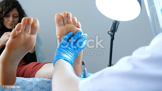 938027870 istock photo Pedicure master produces hardware peeling on the client's feet 1155595260