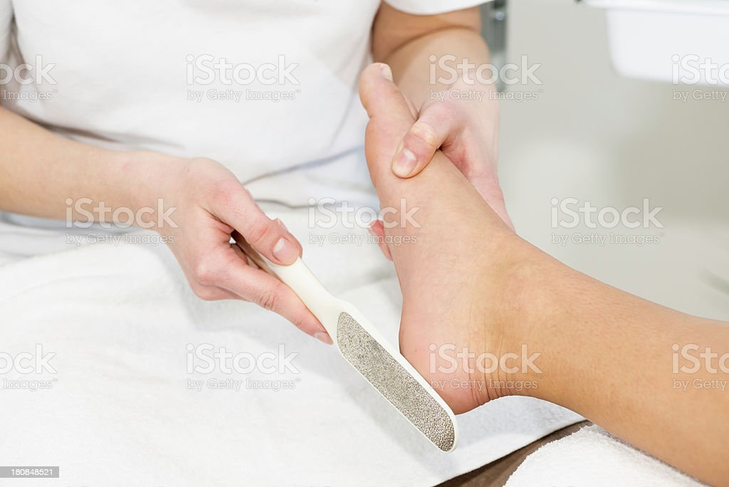 Pedicure treatment - scrubbing heels royalty-free stock photo