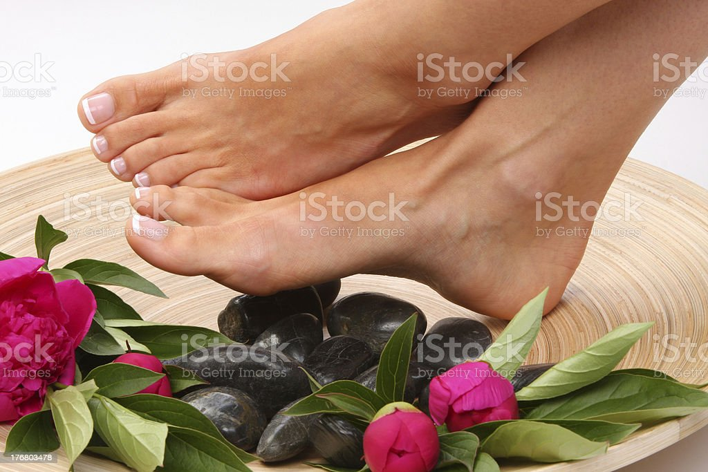Pedicured feet with stones and flowers stock photo