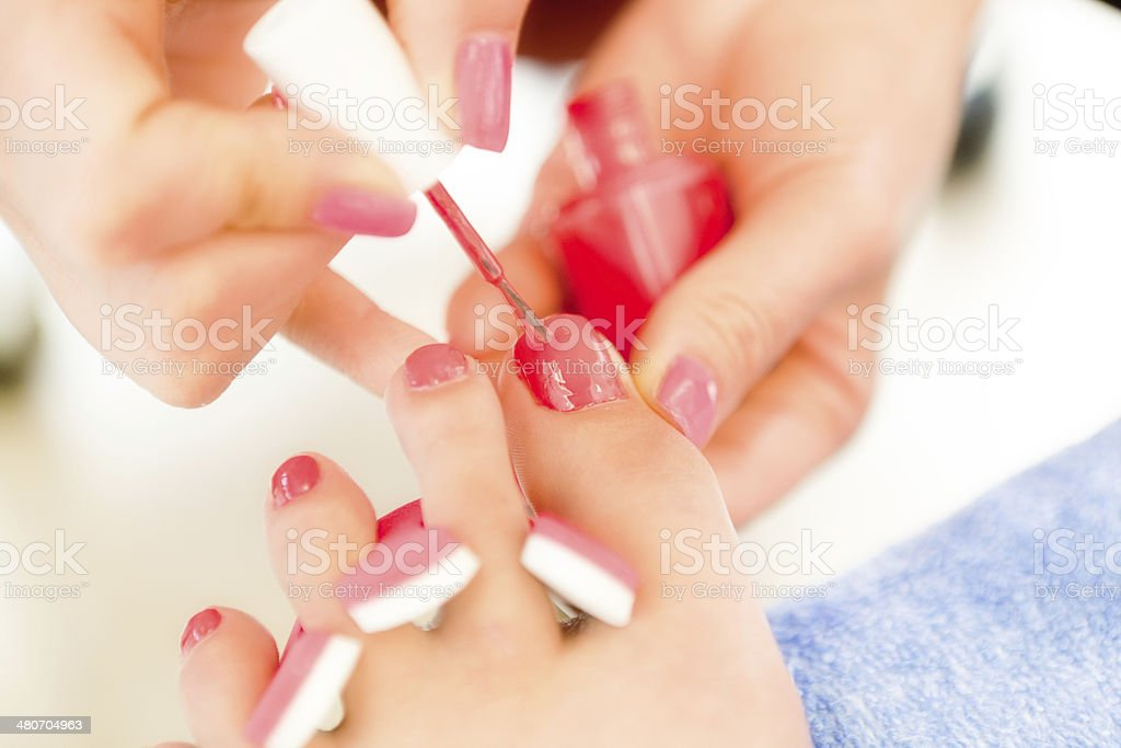 Close up of a pedicurist\'s hands applying finishing touches on...