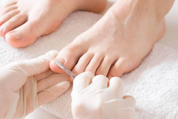 Pedicurist's hands in protective rubber gloves cutting toenails with scissors. Cares about man's feet. Specialist with client in beauty salon. Professional beauty service. Pedicure, manicure concept. Pedicurist's hands in protective rubber gloves cutting toenails with scissors. Cares about man's feet. Specialist with client in beauty salon. Professional beauty service. Pedicure, manicure concept. pedicure manicure men beauty spa stock pictures, royalty-free photos & images