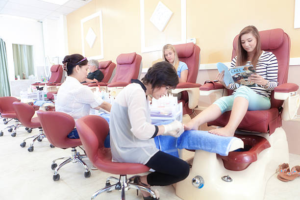 fachkräften für maniküre und pediküre mit kunden im nail spa salon horizontal - nailstudio stock-fotos und bilder