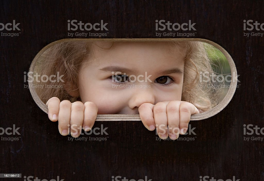 Peek-a-boo! Little girl looking out royalty-free stock photo