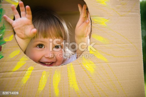 Little child looking through window of children's house made of big box