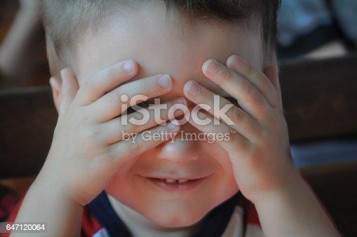 Close up of toddler boy playing peek-a-boo.