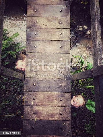 Two boys peeking from beneath a wooden foot bridge above a flowing stream in a forrest garden during a session of hide and seek being found with smiles on their faces Cape Winelands Cape Town South Africa
