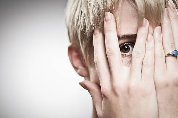 Peeking Fearful girl peeking through her fingers. hide and seek stock pictures, royalty-free photos & images