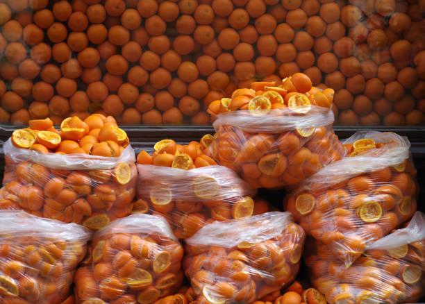 schälen für den saft von orangen in plastiktüten auf dem hintergrund einer großen anzahl von frischen orangen gepresst - orangenscheiben trocknen stock-fotos und bilder