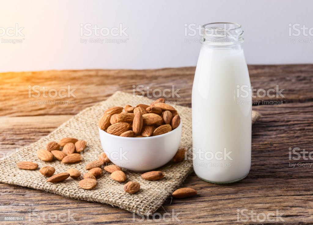 Peeled almonds with bowl and Bottle of almond milk on rustic wooden stock photo