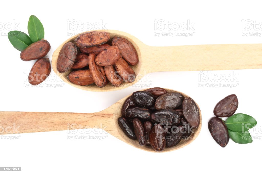 peeled and unpeeled cocoa beans in a wooden spoon with leaf isolated on white background close-up top view stock photo