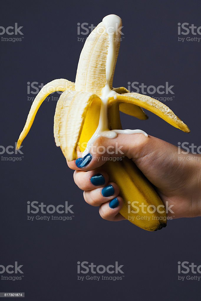 peeled banana ejaculates with yogurt stock photo