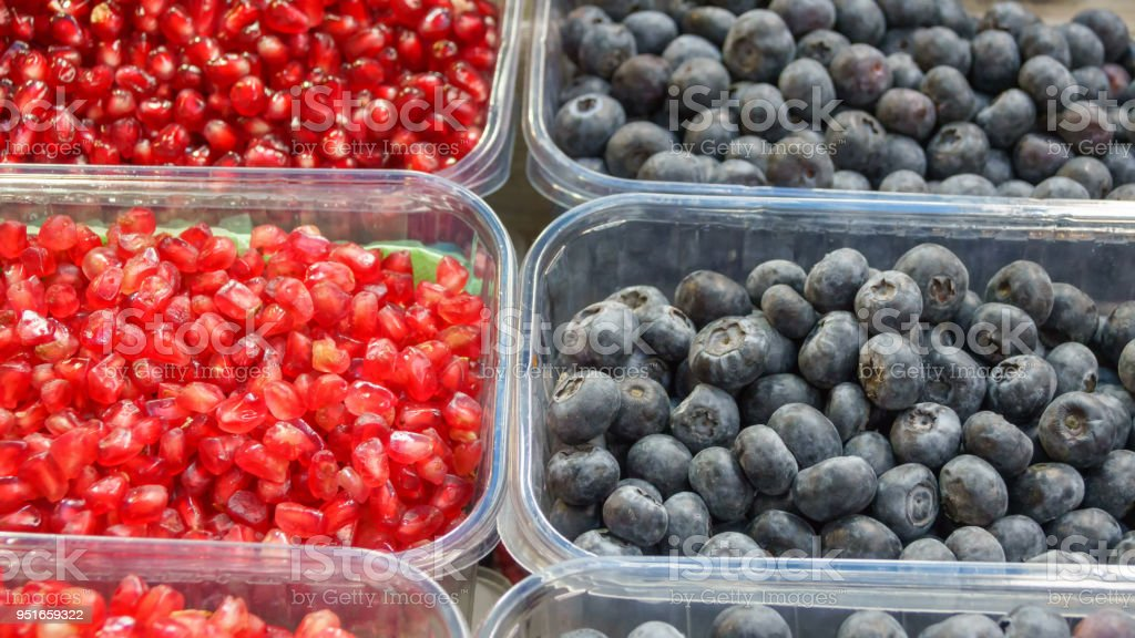 Peeled berries of pomegranate and blueberries stock photo